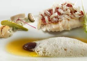 Salmonetes con cristales de escamas comestibles, jugo de pescados de roca al azafrán, bombón líquido de olivas negras
